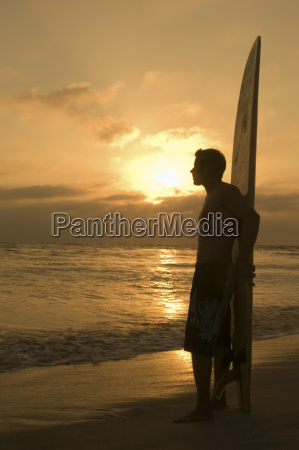 man with surfboard watching sunset on