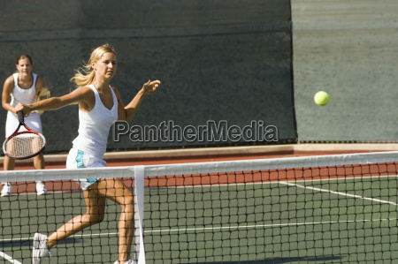 doubles player hitting tennis ball with