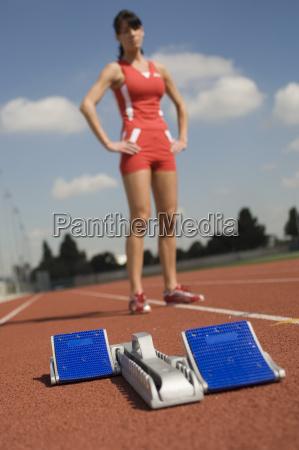 startblock mit sportlerin im hintergrund