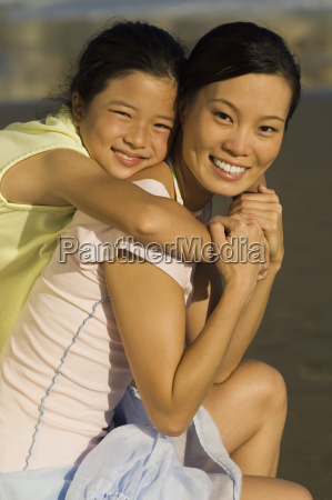 girl embracing mother on beach