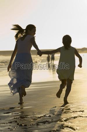 mutter und tochter am strand laufen