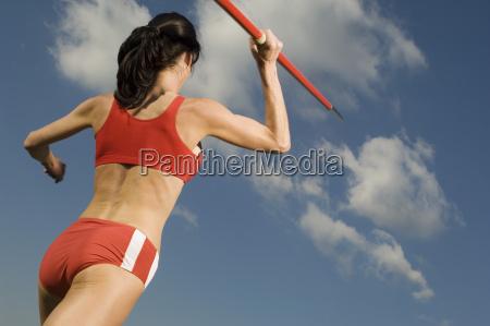female athlete throwing javelin against sky