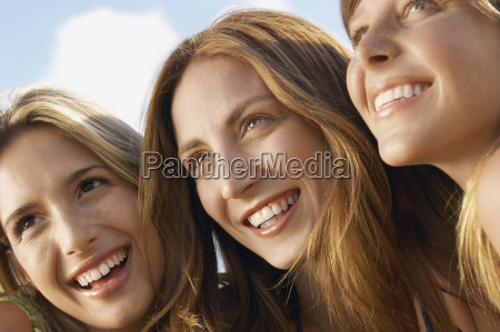 female friends looking away while smiling