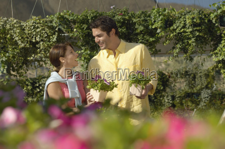 mature couple buying flower plants
