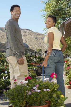 couple pulling cart full of potted
