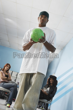 man bowling with female friends in