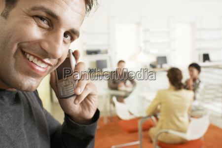 smiling businessman using mobile phone in