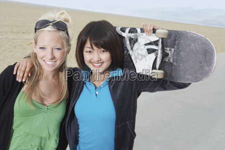 happy female friends holding skateboard