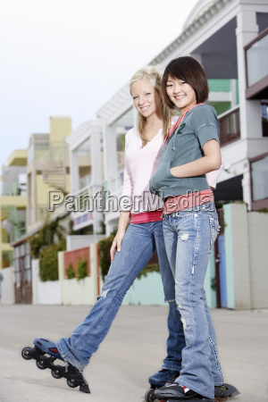 female friends rollerblading on street