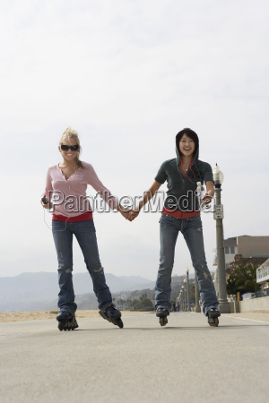 junge frauen rollerblading on street