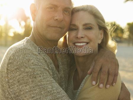 happy senior couple embracing on beach