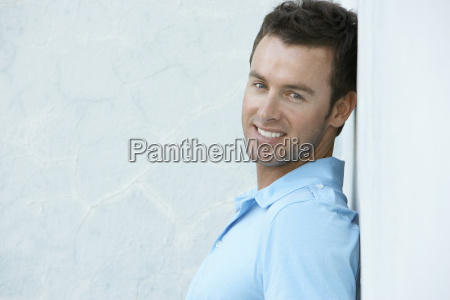 happy young man leaning against wall