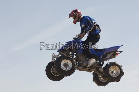 man riding quad bike in midair