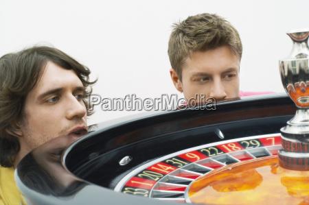 hoffnungsvolle, männer, die, roulette-rad-drehbeschleunigung, aufpassen - 21416863