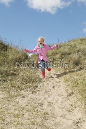 girl running down sand dunes