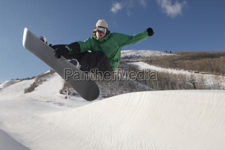 junger snowboarder der bremsungen auf snowy