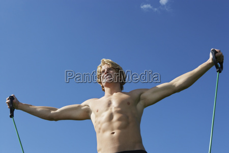 caucasian man exercising against blue sky