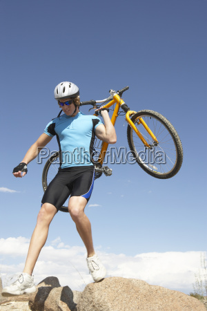 young man carrying bicycle on rocks