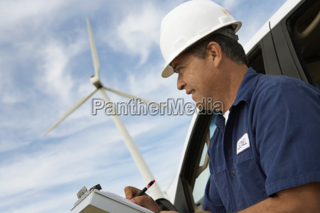 engineer writing on clipboard at wind