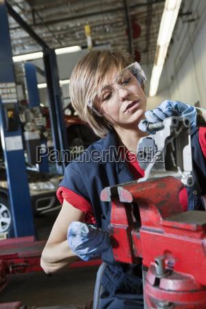 junge mechanikerin in der schutzwussarbeit in