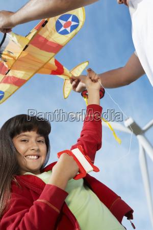 girl holding airplane kite at wind