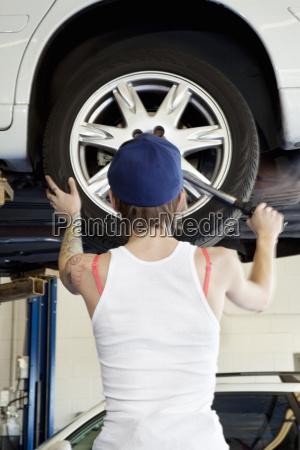 rueckansicht der jungen weiblichen mechaniker arbeiten