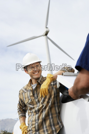 engineers near wind turbine at wind