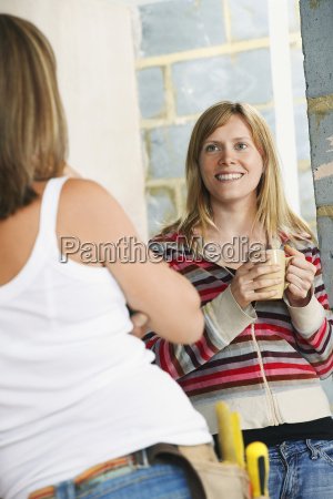 woman with toolbelt talking to smiling