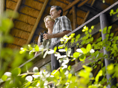 couple on terrace with binoculars
