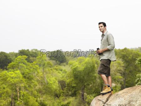 man on rock with binoculars looking