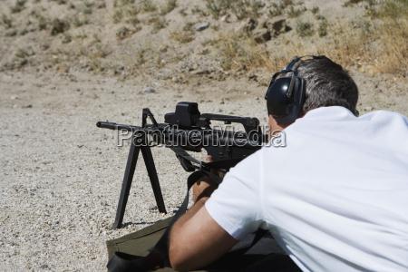 mann der maschinengewehr auf schiessstand zielt