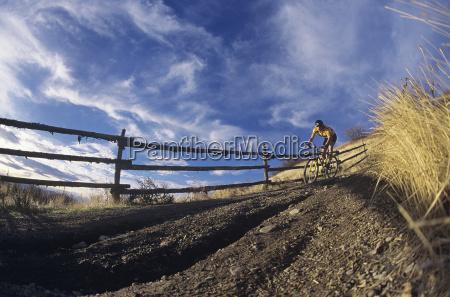 man mountain biking along country path