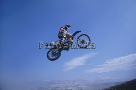 mountain biker jumping against blue sky