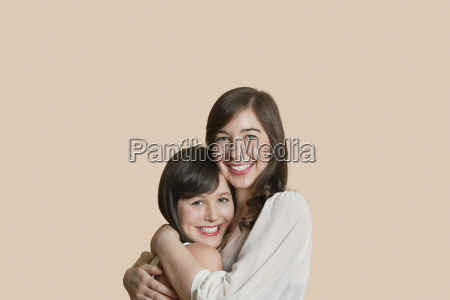 portrait of young female friends hugging
