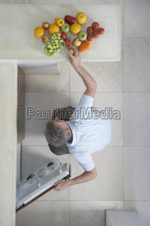 man putting fruits in refrigerator