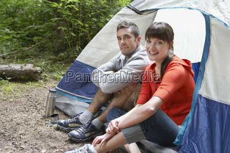 portrait of couple sitting by tent