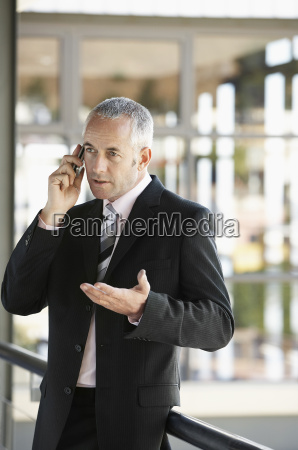 businessman gesturing while using cell phone