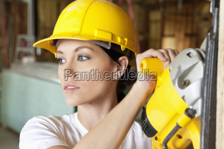 female construction worker cutting wood with