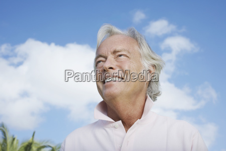 mature man smiling against sky