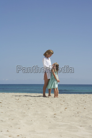mother and daughter standing on sunny