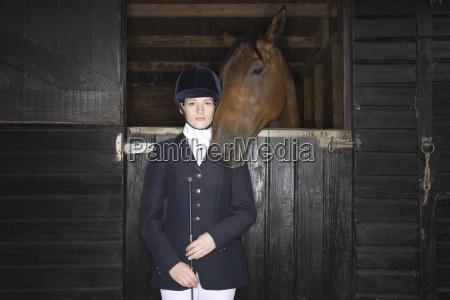 weiblicher reiter mit pferd im stall