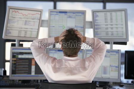 stock trader watching computer screens with