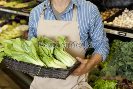 midsection of man holding basket of