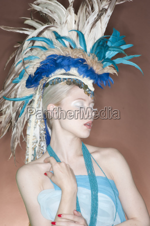 beautiful young woman wearing feather headgear