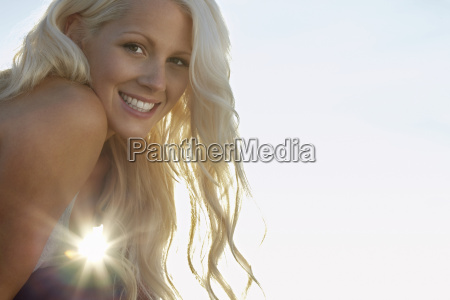 attractive woman smiling against clear sky