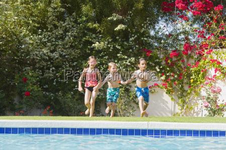 kinder laufen in richtung schwimmbad