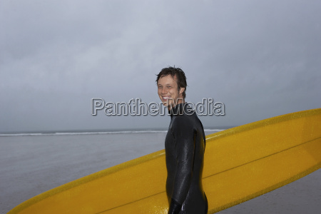happy man with surfboard standing at