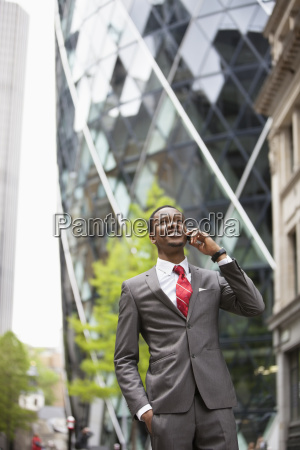 happy african american businessman using cell