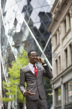 happy businessman using cell phone outside