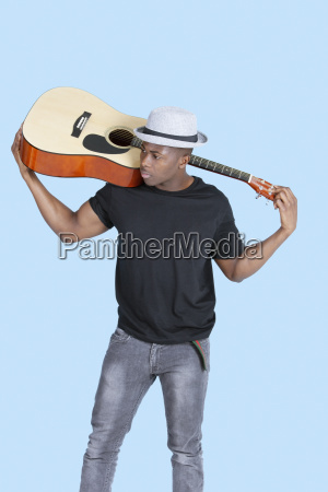 young african american man carrying guitar